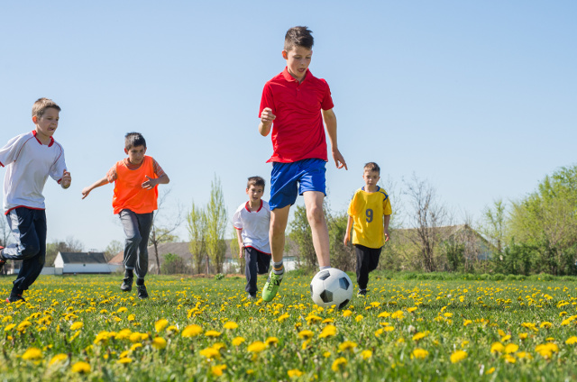 Boys kicking football on the  field vitamin d deficiency